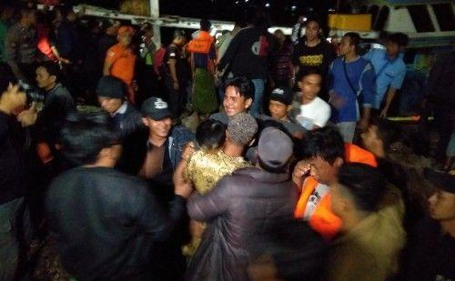 DISAMBUT TANGIS: Kerabat membantu polisi mengevakuasi korban KM Santika Nusantara.