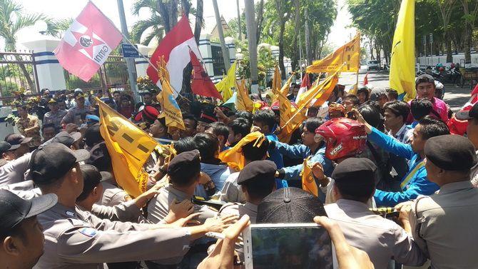 ADU KUAT: Mahasiswa saling dorong dengan polisi di depan pintu kantor DPRD Sampang kemarin.