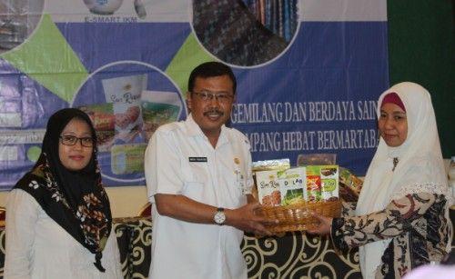 SIMBOLIS: Kepala Disperdagprin Sampang menyerahkan produk ke perwakilan IKM.