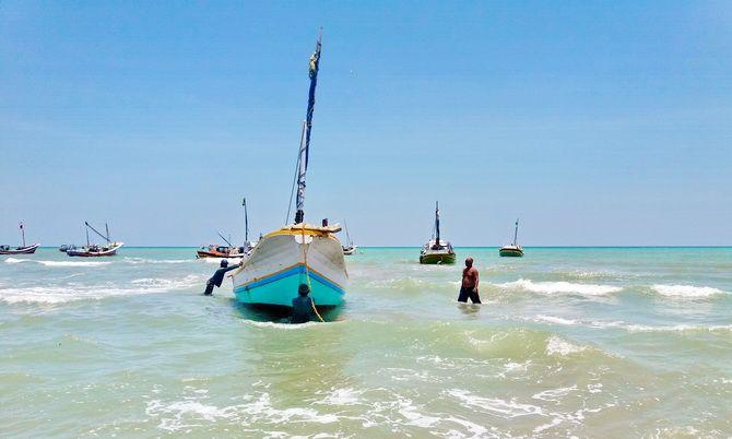 KANDAS: Nelayan mendorong perahu yang tertambat batu di pesisir Desa Branta Pesisir, Kecamatan Tlanakan, kemarin.