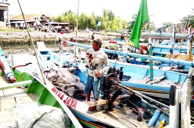 BUTUH KEPASTIAN: Andi, nelayan asal Kampung Bandaran, Kelurahan Pejagan, Kecamatan Kota Bangkalan, berada di perahu kemarin.