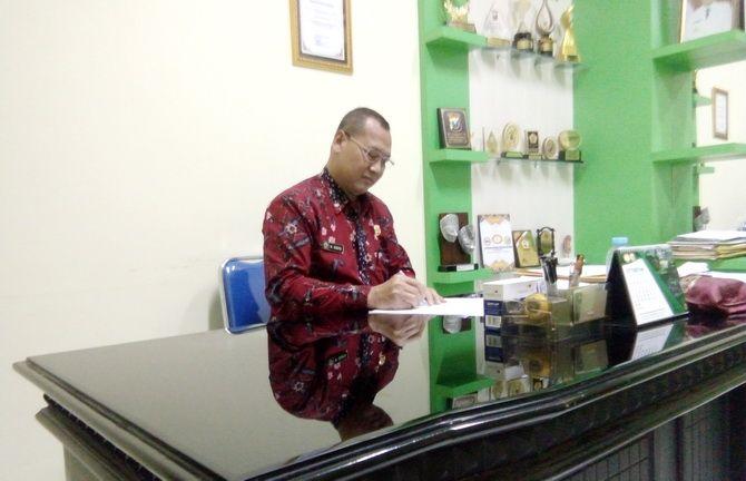 SIBUK: Kepala Dinkes Bangkalan Sudibyo menandatangi sejumlah berkas di ruang kerjanya kemarin.