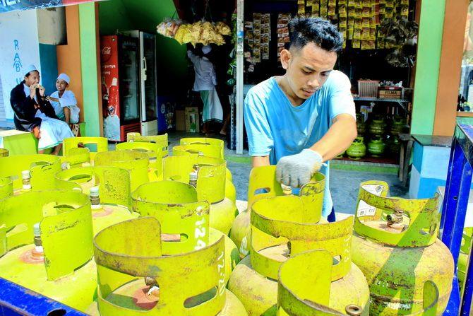 KERJA KERAS: Warga mengangkut tabung elpiji 3 kg di Jalan KH. Moch. Yasin, Bangkalan, Jumat (18/10).