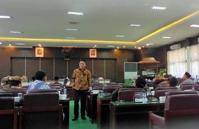 LAMBAN: Hamdi, anggota tim penyusun tatib DPRD Pamekasan berbincang dengan anggota tim lainnya usai rapat tertutup kemarin.