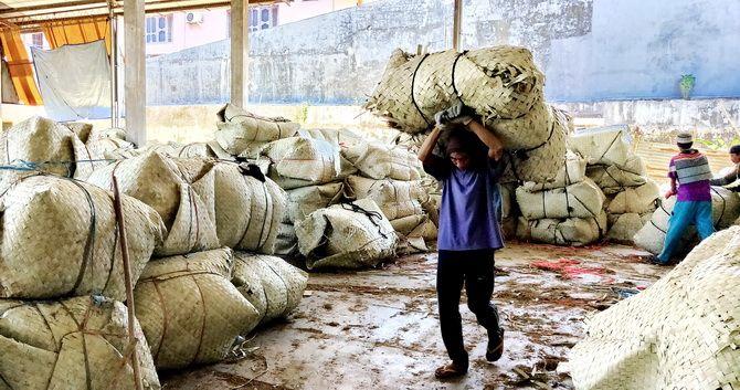 KERJA KERAS: Kuli memanggul tembakau di gudang pribadi milik M. Suli Faris, Desa Buddagan, Kecamatan Pademawu, Pamekasan, beberapa waktu lalu.
