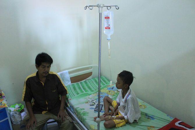 MULAI MEMBAIK: Abd. Malik ditemani ayah angkatnya, Nasirudin, di ruang privasi anak lantai 3 RSUD Syamrabu Bangkalan kemarin siang.