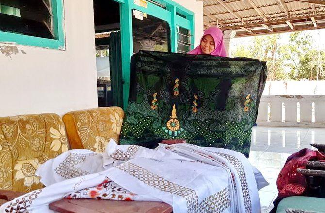 MENGANDUNG SEJARAH: Aminatuttaqiyah menunjukkan hasil produksi Batik Trunojoyo, Kamis (14/11).