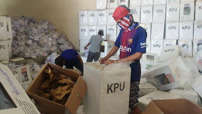 SIAP LELANG: Pekerja membongkar tumpukan kotak suara yang ada di gudang logistik KPU Sampang kemarin.