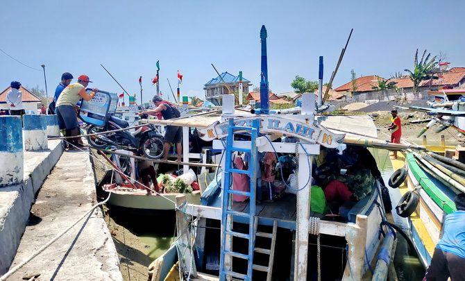 BERSANDAR: Warga menaikkan kendaraannya ke perahu di Pelabuhan Tanglok kemarin.