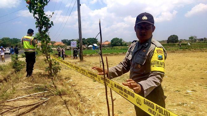 BERKEMBANG: Anggota Reskrim Polres Sampang memasang garis polisi di tanah sengketa beberapa waktu lalu.