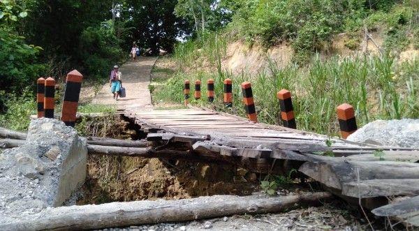 BERBAHAYA: Warga hendak melintas di jembatan kayu hasil swadaya pasca ambruk.