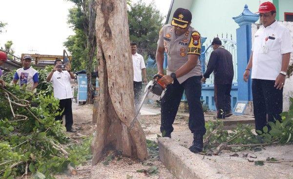 BERKERINGAT: Kapolres Sumenep AKBP Deddy Supriadi saat menebang pohon pakai gergaji, Rabu (8/1).