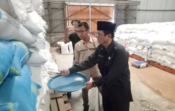 PERIKSA: Ketua DPRD Sumenep Abd. Hamid Ali Munir mengecek kualitas beras di gudang Bulog kemarin.