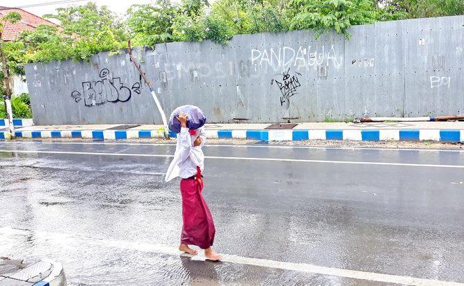 GEMBIRA: Siswa SD berjalan di bawah guyuran gerimis sepulang sekolah di Jalan Rajawali kemarin.