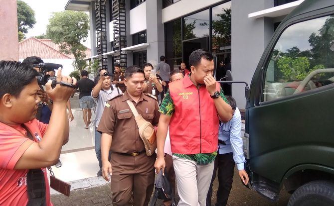 MENUJU TAHANAN: Tersangka Mukmin Hanafi (mengenakan rompi tahanan) digelandang ke mobil tahanan di kantor Kejaksaan Negeri Sumenep kemarin.