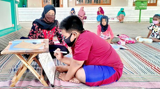 TETAP SEMANGAT: Siswa kelas 2 SDN Manding Laok 1 belajar di halaman Masjid Besar Babul Jannah Manding, Sumenep,disaksikan wali murid mereka kemarin.