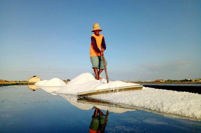 DI BAWAH TERIK MATAHARI: Petani mengais garam di tambaknya di Desa Bunder, Kecamatan Pademawu, Pamekasan, kemarin.