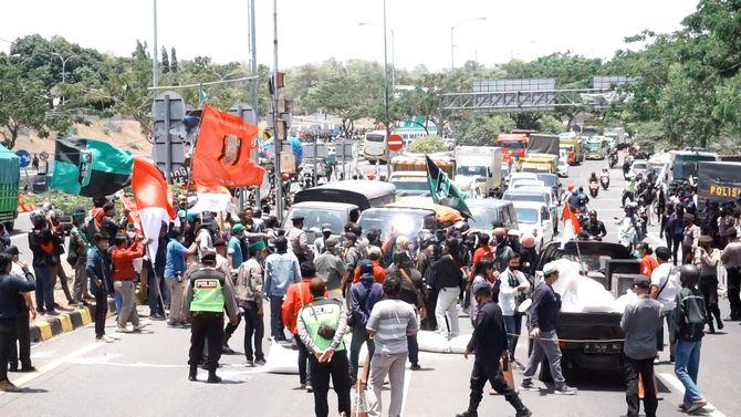 BLOKADE: Massa Aliansi Trunojoyo Bergerak memblokir jalan di pintu masuk Jembatan Suramadu sisi Madura di Desa Morkepek, Kecamatan Labang, Bangkalan, kemarin.