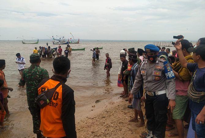 SITA PERHATIAN: Warga dikawal anggota TNI-Polri menyaksikan proses evakuasi jenazah Sawawi, 25, di perairan Desa Jadung, Kecamatan Dungkek, Sumenep, kemarin.