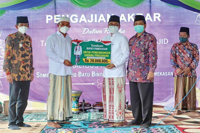 SUPPORT: Bupati Pamekasan Baddrut Tamam (berkacamata) didampingi Kabag Kesra Halifaturrahman menyerahkan bantuan kepada Pimpinan Ponpes Darul Karomah KH. Mudassir Fatholbari kemarin.