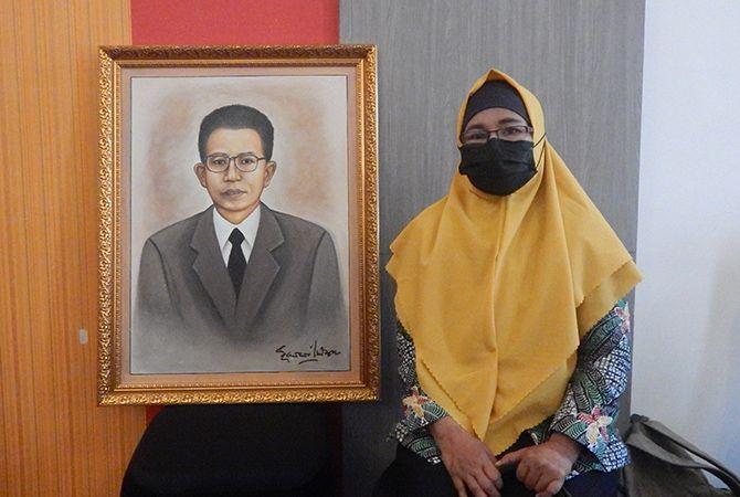 INSPIRATIF: Ratna Susilowati, keponakan M. Tabrani, berfoto dengan lukisan M. Tabrani karya budayawan D. Zawawi Imron di Pamekasan, Selasa (30/3).
