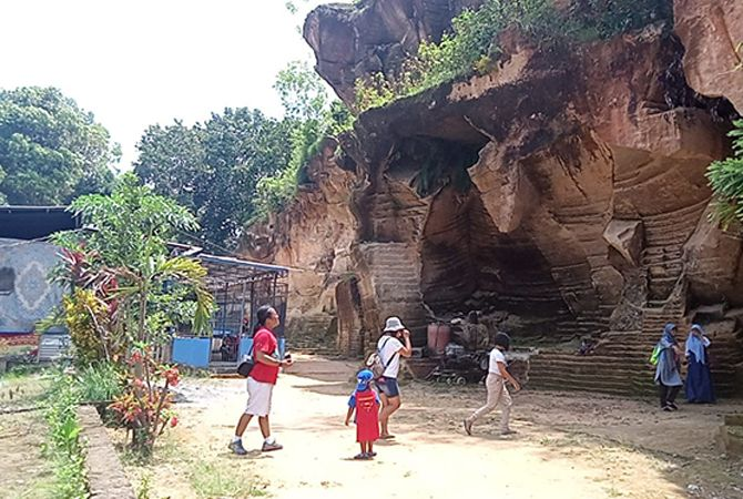 BERFOTO RIA: Pengunjung dari Sidoarjo berfoto ria dengan latar pemandangan Bukit Kapur yang terletak di Desa Berbeluk, Kecamatan Arosbaya, Bangkalan, kemarin.