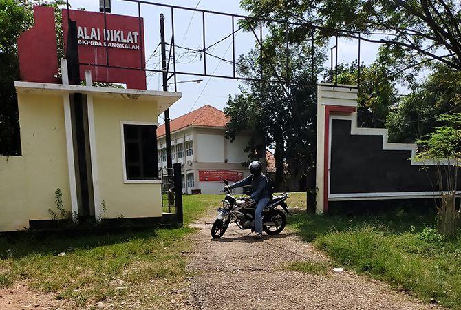 SEPI: Seorang pengendara sepeda motor berada di depan tempat karantina PMI yang dipulangkan dari balai diklat.