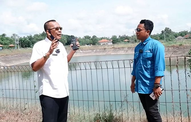 SUKSES: PJ JPRM Digital Prengki Wirananda berbincang dengan Direktur Perumda Tirta Jaya Pamekasan Agoes Bachtiar di sekitar Embung Samiran, Desa Kodik, Kecamatan Proppo.