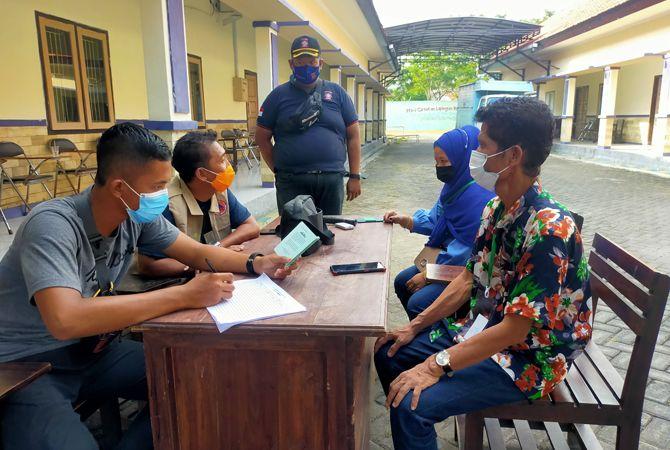 DIDATA: Petugas BPBD Sampang mencatat identitas Rinawati dan Munir, PMI yang baru tiba di BLK kemarin.