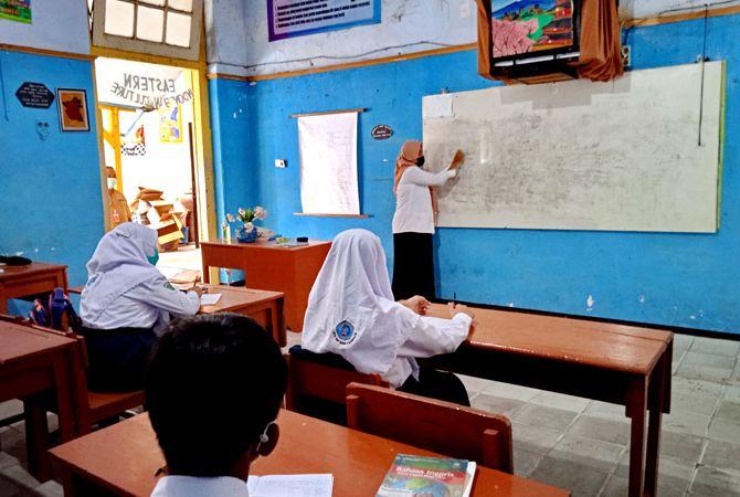 HARUS DARING LAGI: Seorang guru SMPN 2 Bangkalan menjelaskan mata pelajaran di depan siswa, Senin (31/5).