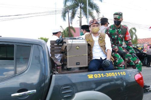 TURUN LANGSUNG: Bupati Bangkalan Abdul Latif Amin Imron duduk di atas mobil Polsek Arosbaya saat melintas di Desa Tengket, Kecamatan Arosbaya.