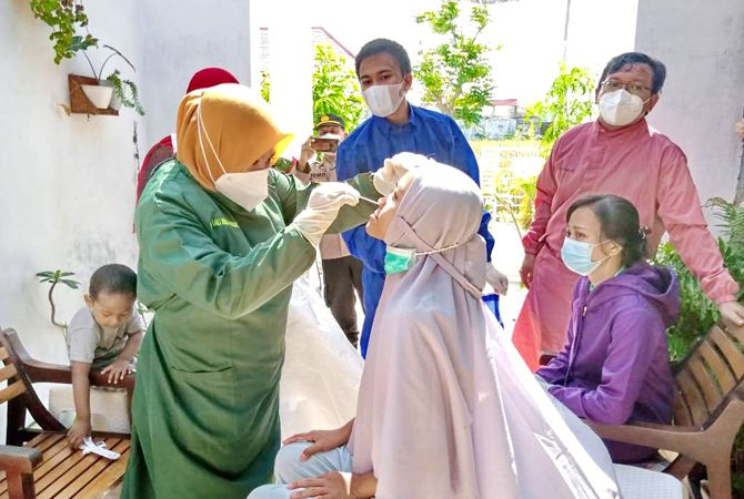 PROSES LACAK: Tim Tracing Puskesmas Kamoning melakukan tes swab kepada keluarga pasien Covid-19 yang meninggal kemarin.