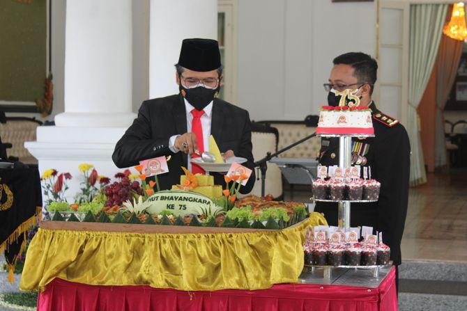 VIRTUAL: Bupati Abdul Latif Amin Imron memotong tumpeng sebelum diberikan kepada Kapolres AKBP Alith Alarino pada peringatan HUT Ke-75 Bhayangkara di Pendapa Agung Bangkalan kemarin.