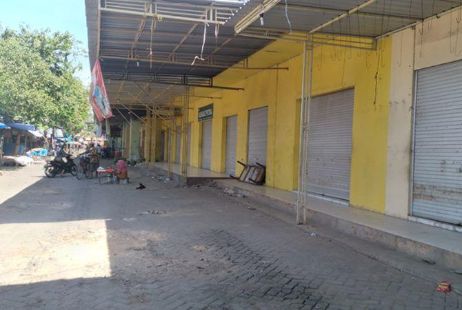 KOMPAK TUTUP: Tukang becak sedang melintas di sekitar toko dan lapak pedagang yang tutup di Pasar Anom Baru Sumenep kemarin.