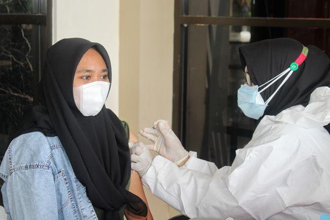 BUTUH PERHATIAN: Seorang tenaga kesehatan menyuntikkan vaksin kepada warga di Gedung Serbaguna Rato Ebuh Bangkalan, Senin (12/7).