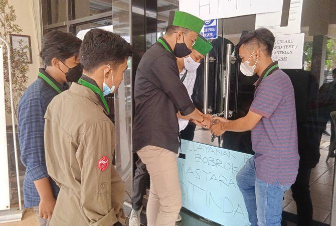 DISEGEL: Pengurus HMI Cabang Bangkalan memasang gembok di pintu utama kantor BPN kemarin.