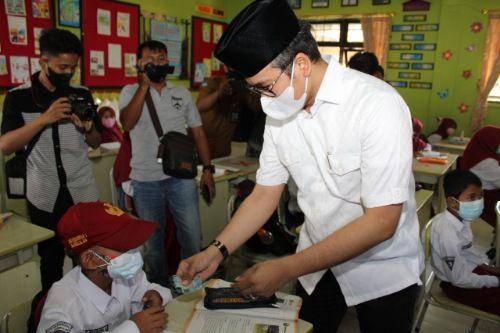 SAYANG GENERASI PENERUS: Bupati Bangkalan R. Abdul Latif Amin Imron menyerahkan uang saku kepada murid SDN Kemayoran 1 yang mengikuti PTM, Senin (6/9).
