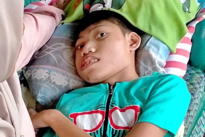 BUTUH ULURAN TANGAN: Kiki saat berbaring di ruang tengah rumahnya di Desa Waru Barat, Kecamatan Waru, Pamekasan, kemarin.