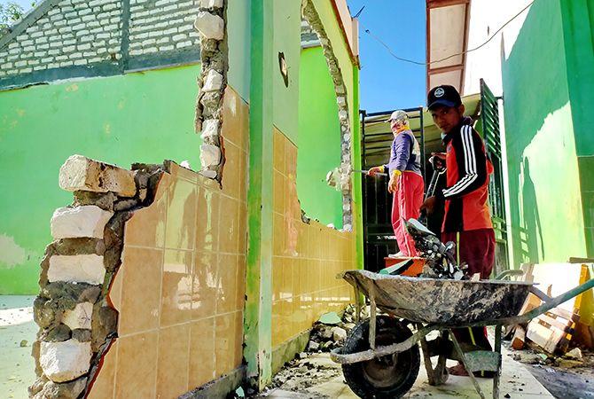 KERJA KERAS: Pekerja membongkar gedung perpustakaan SDNGunung Sekar 2, Sampang, yang akan diperbaikikemarin.