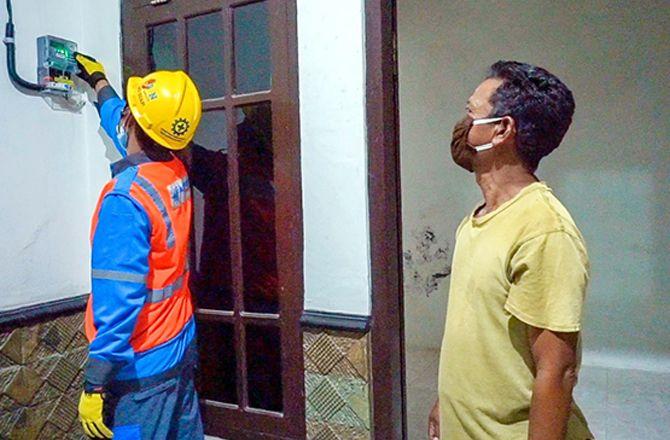 MENYALA: Petugas mengecek kWh listrik pelanggan di Pulau Kangean, Sumenep.