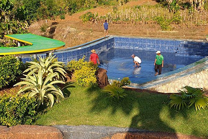 PERLAHAN: Beberapa warga berada di lokasi pembangunan kolam renang di objek Wisata Bukit Kehi, Desa Kertagenna Daya, Kecamatan Kadur, Pamekasan.
