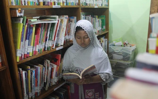 Siswa SD membaca buku di perpustakaan keliling di Kelurahan Blooto, Kec. Prajurit Kulon, Kota Mojokerto.