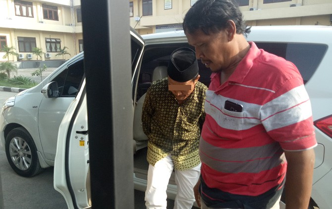 AJ (kiri) turun dari mobil dan digelandang petugas menuju ruang Unit PPA Satreskrim Polres Mojokerto.