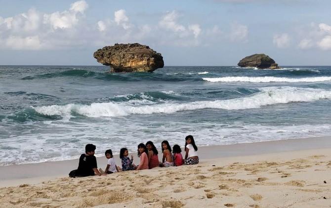 Wisatawan anak-anak menikmati pesona Pantai Sraun Pacitan.