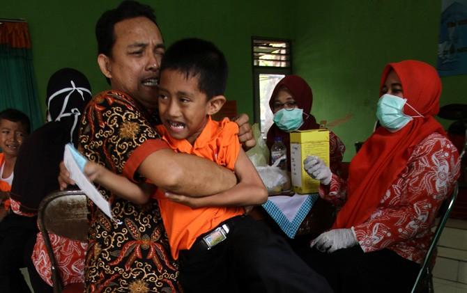Seorang guru memegang siswa yang akan menjalani suntik ORI di SDN Kranggan 1 Kota Mojokerto.
