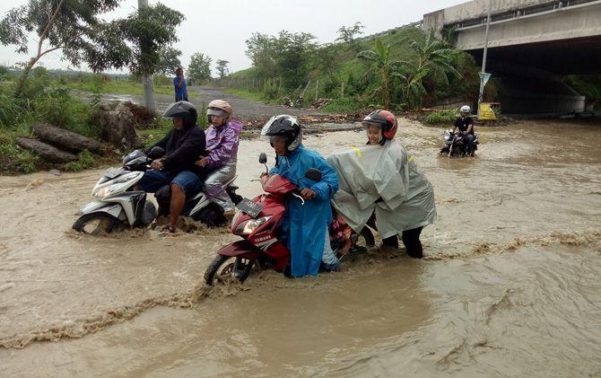 Sejumlah pengendara terpaksa mendorong sepeda motornya setelah nekat menerobos banjir di Jalan Raya Jetis, Kabupaten Mojokerto.