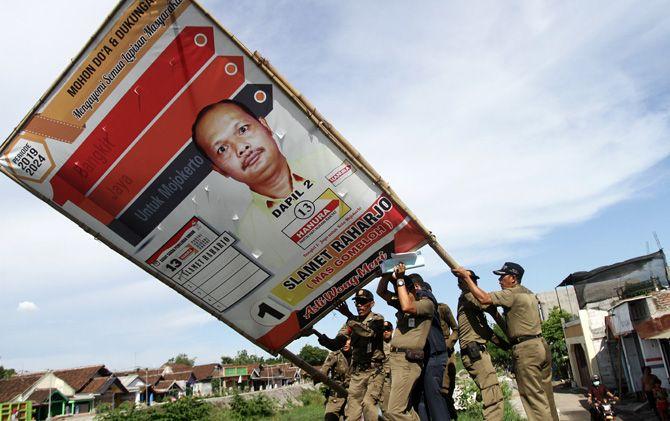 Petugas Satpol PP Kota Mojokerto menertibkan banner caleg yang dianggap melanggar ketentuan.