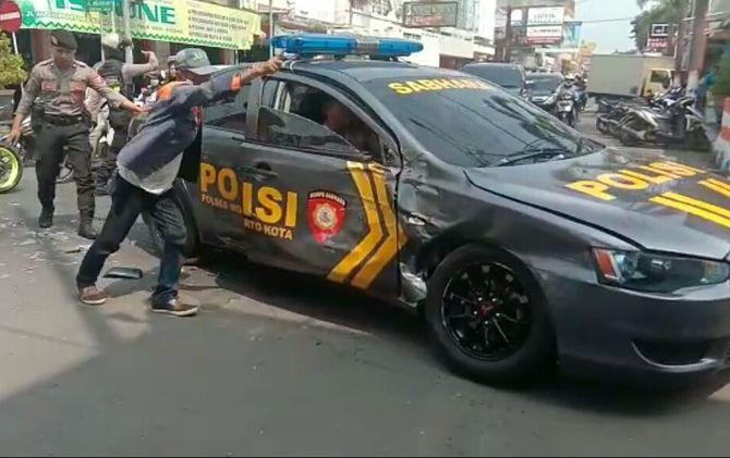 Mobil patroli Satsabhara Polresta Mojokerto ditepikan petugas jukir dan petugas usai mengalami kecelakaan.