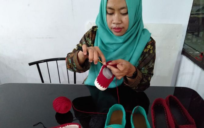Febri Martha menunjukkan sepatu rajut hasil karyanya.
