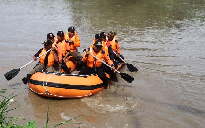 Tim gabungan mendayung perahu karet menyusuri sungai.
